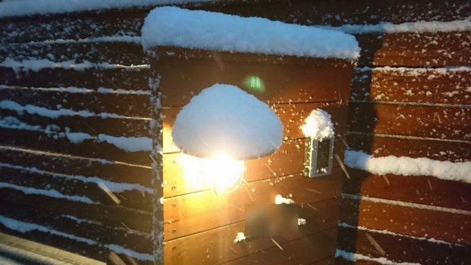 木製門柱の笠木とマリンランプに雪が積もる