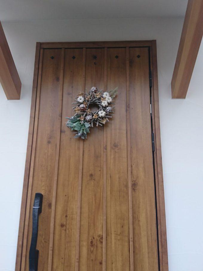 木目の玄関ドアに玄関リース冬バージョン